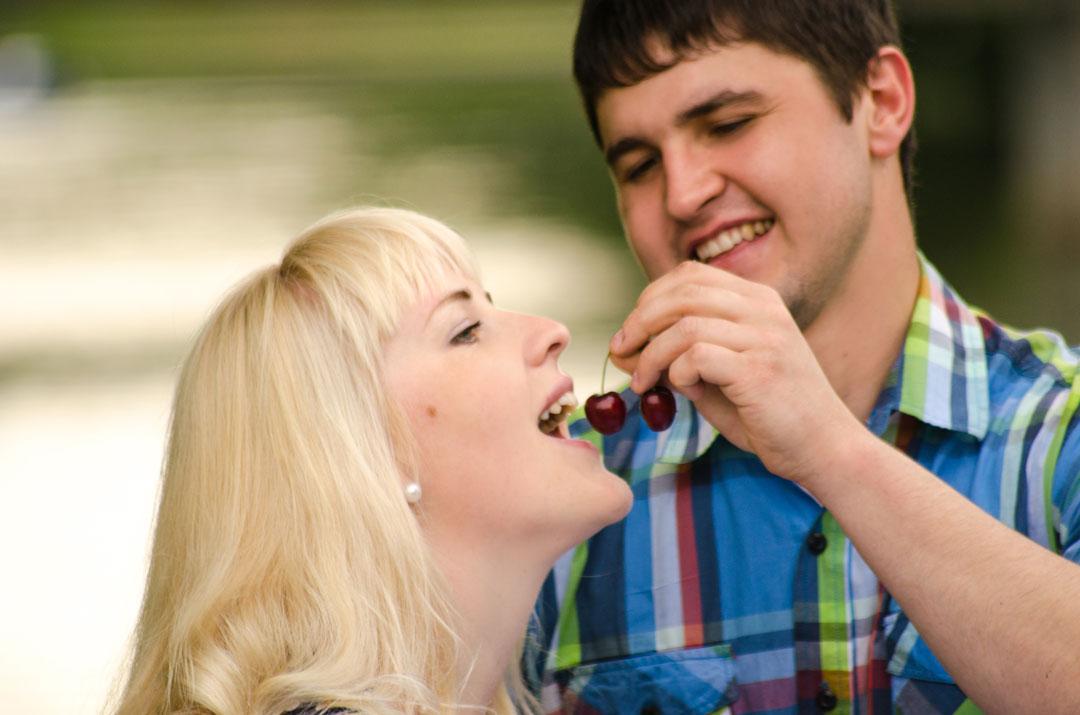 Парень кормит девушку вишней